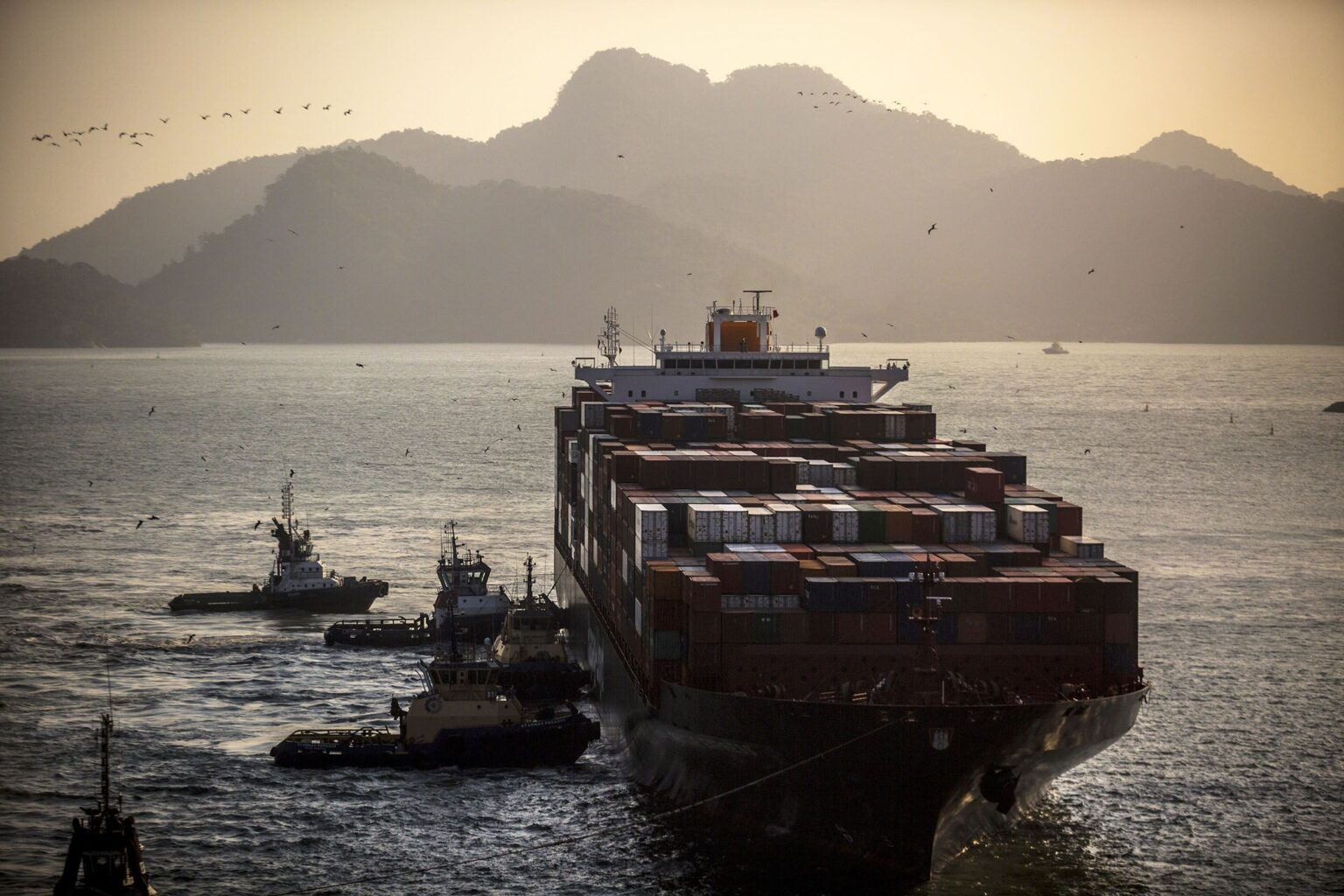 Tugs carrying a ship into the harbor in rio - data analytics